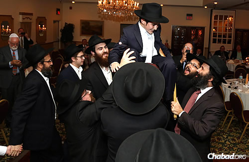A bar mitzvah tradition: up in the chair for the young man of honor.