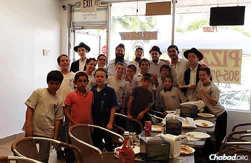 Kids after a mitzvah tank parade on Tuesday, letting people know about the Friday-night seder and giving out shmurah matzah. Afterwards, Rosenberg and Kamish, in the back row with friends, took them out for pizza.