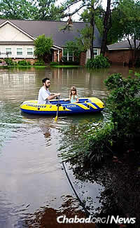 Joseph Rosenzweig and his daughter, Yael, survey floodwaters in front of his in-laws' home near Brays Bayou. The photo was taken by his wife, Noa, who was inside with their baby son.