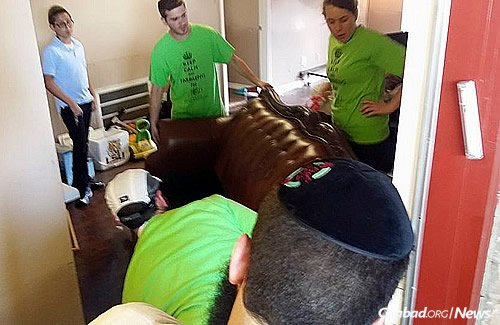 Other young volunteers lift a sofa to remove it from a home.