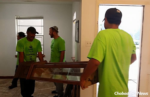 Removing all kinds of furniture, this one a glass piece; the floors show dirt and damage from the floodwaters.