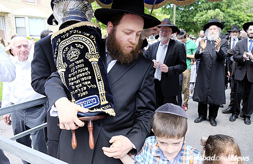 Rabbi Baruch Hertz, rabbi of the Chabad community in Chicago, here with two of his children, noted that the event was the result of an effort spanning the entire community. (Photo: Deja Views)