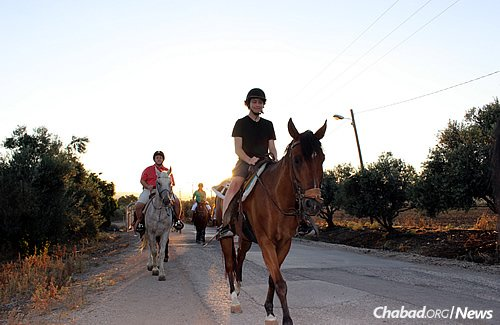 Maddy Cooper enjoys a horse ride, followed by Patrick Tighe and other participants in the Friendship Circle trip.