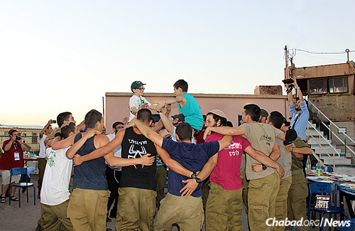 Noah Tighe and Noah Goldberg get lifted by Israeli soldiers at a barbecue event held on an army base.