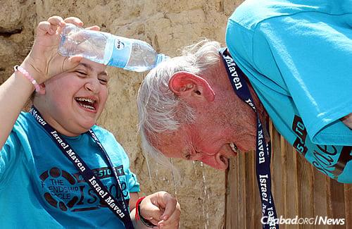 Carlie Suris cools off her grandfather, Marvin Berman, at Masada.