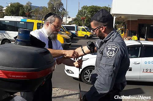 Raichik helps a border policeman don tefillin.