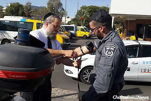 Raichik helps a border policeman in Be'er Sheva don tefillin.