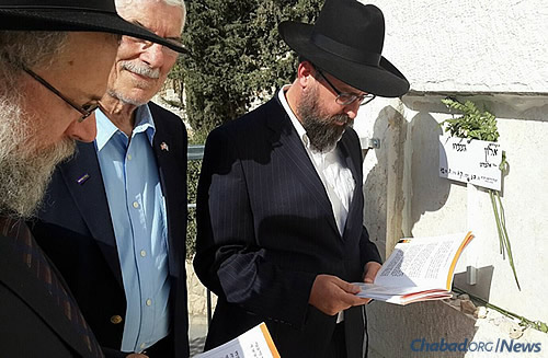 The Raichik group at the grave of Alon Govberg, who was killed in a bus attack one week ago and has no family in Israel. The men organized a minyan at his grave site to say Tehillim and Kaddish, making the end of the shiva (mourning) period.