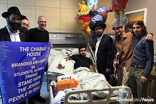 At Hadassah Ein Kerem Medical Center in Jerusalem are Rabbi Peretz Chein, left, executive director of the Chabad House at Brandeis University in Waltham, Mass., who came with a local delegation to visit Israeli terror victims and their families. To his right are Rabbi Menachem Kutner, director of the Chabad Terror Victims Project; Rabbi Yisroel Naftalin, the hospital's Chabad emissary; and Brandeis student Tzvi Miller, far right, with his brother, Netzach, who lives in Israel.