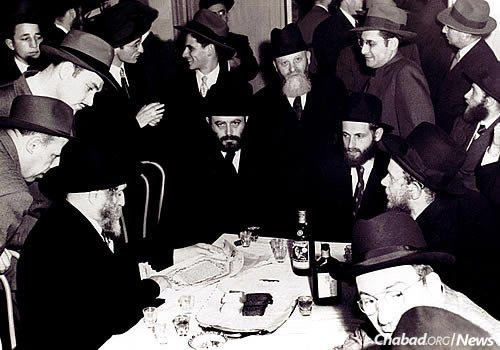 At his wedding reception,Feigelstock is flanked by the Rebbe and Rabbi Menachem Zeev (Volf) Greenglass. Standing behind him is his father, with whom he had recently reunited after years of separation.