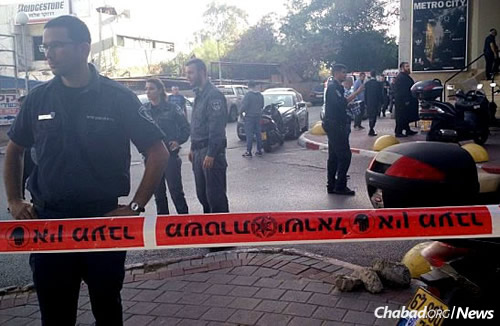 Police at the scene where two men were killed after leaving afternoon prayer services in a Tel Aviv office building.