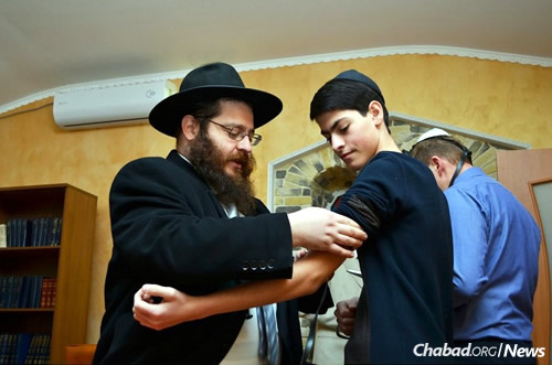 Rabbi Ruppo helps a young man wrap tefillin.