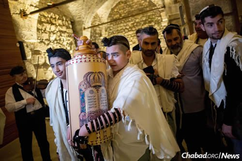 13-year-old Naor Shalev Ben-Ezra carrying a Torah scroll as he celebrates his Bar Mitzvah with family and friends at the Western Wall in Jerusalem's Old City . Naor Shalev was critically injured in a stabbing attack in Pisgat Zeev in Jerusalem over two mothes ago. (Photo: Yonatan Sindel/Flash90)