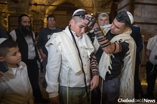 Wrapping tefillin before being called to the Torah.