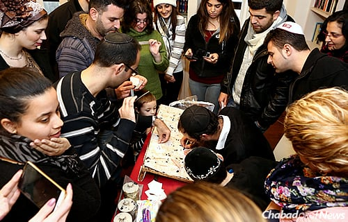 Students at the Netanya Academic College in Israel gather around Rabbi Shneur Simcha Landa and his children. They have been signing up to perform mizvahs in memory of their friend and fellow student, Alon Bakal, who was slain by a terrorist in Tel Aviv.