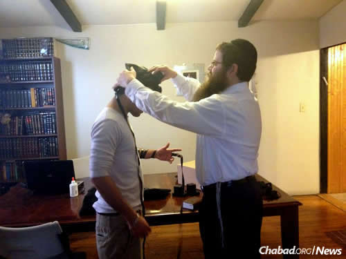The rabbi wraps tefillin with a student.