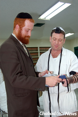 The rabbi wraps tefillin with a man in the Koher Unit, one of four prisons that cater to the needs of Jewish inmates in Texas.