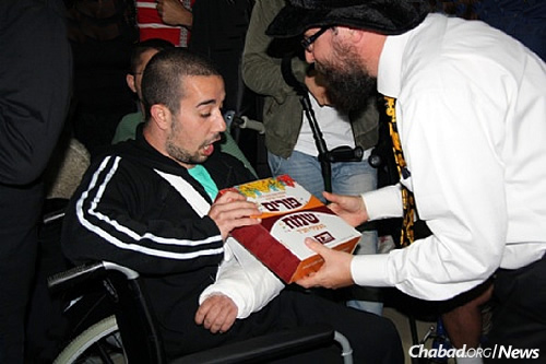 Rabbi Menachem Kutner, director of the Chabad Terror Victims Project, gives a welcome Purim package to a soldier at Sheba Medical Center in Ramat Gan visibly glad to see him. From the moment of injury, CTVP is at their bedside in the hospital, during rehabilitation and for as long as needed. (File Photo/CTVP)