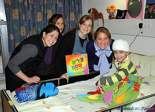 Volunteers with the Chabad Terror Victims Project in Israel visit Orel Elazarov, who was wounded in the head by a rocket in Beersheva years ago. They bring Purim packages to individuals and families for the holiday and spend time with them during the long recovery process. (File Photo/CTVP)