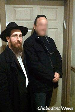 Rabbi Chaim Scheiman assists an ex-offender in hanging a mezuzah.