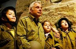 """Yitzchak Yifat está no centro, com lágrimas nos olhos e seu capacete nas mãos em uma das fotografias mais famosas da história de Israel ao lado de seus companheiros do IDF, Haim Oshri e Zion Karasanti. """"Paraquedistas no Muro das Lamentações"""" foi registrada por David Rubinger no momento em que se dirigiram ao Muro das Lamentações depois da libertação de Jerusalém durante a Guerra dos Seis Dias. O ex-paraquedista Dr. Yitzhak Yifat reviveu a foto após 49 anos com os netos ao seu lado."""
