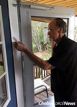 David affixes a mezuzah to his doorpost.