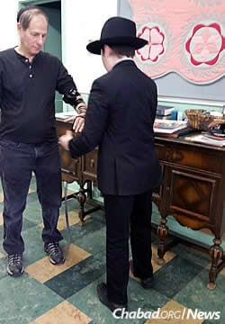 The Katzman family, Chabad-Lubavitch representatives to Nebraska, have made trips to visit the Jews of South Dakota for decades. Here, one of the Katzman boys wraps tefillin with a man in Aberdeen, S.D.
