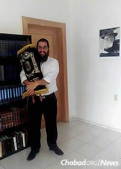 Rabbi Shneur Hecht holds their Torah