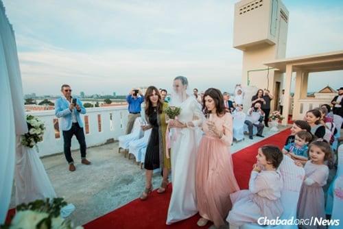 Mashie Butman and Mushka Hecht escort the bride to the chuppah.