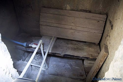 The inside of Natasha Yakovenko's crude, homemade bomb shelter. She and her daughter used to run in there all the time, but now, acclimated to the constant sound and impact of nearby heavy artillery fire, they go only when the situation becomes intense. (Photo: Avraham Edery for Chabad.org)
