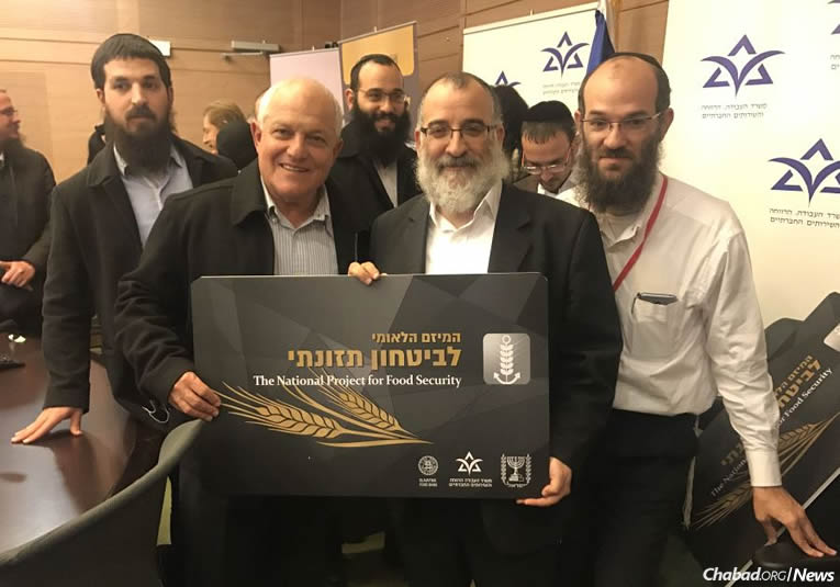 Israel's Welfare and Social Services Minister Haim Katz, left, holds a display card with Rabbi Mendy Blau, director of Colel Chabad's Israel programs, at the Knesset for the launch of a major food-security initiative. (Photo: Welfare and Social Services Ministry)