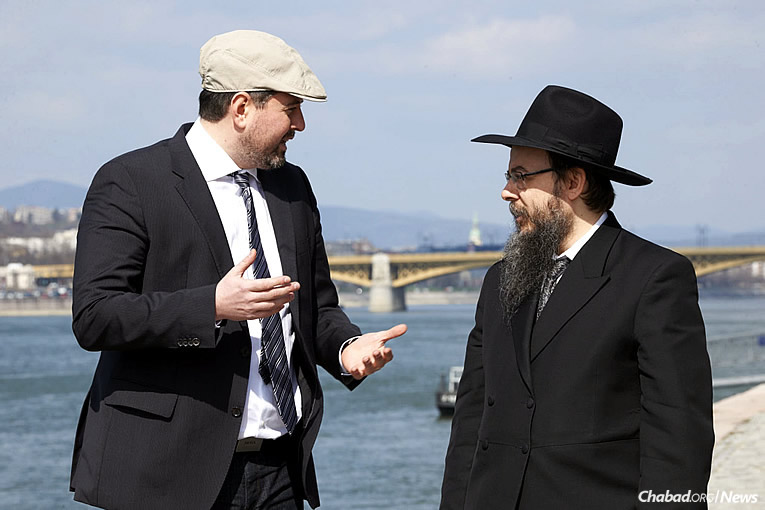 Csanád Szegedi, left, was a Hungarian Neo-Nazi leader until he discovered his Jewish roots. Here, he stands with Chabad Rabbi Boruch Oberlander on the banks of the Danube River, where hundreds of Hungarian Jews were shot between 1944 and 1945. (Photo: Kino Lorber)