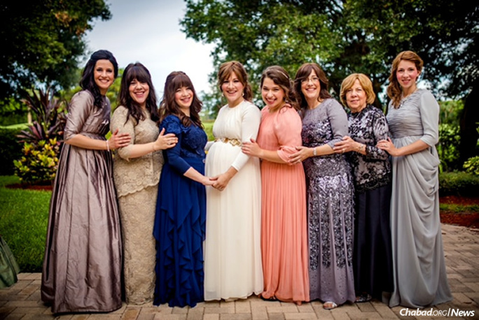 Seven of these eight relatives will spend time together at the annual International Conference of Chabad-Lubavitch Women Emissaries, where many other happy reunions will take place over the next few days in Brooklyn. Pictured at a family wedding are, from left: Dina Hecht, Mushky Laine, Gitty Weinman, Sarale Chanowitz, Bracha Hecht, Bluma Hecht, Susha Alperowitz and Chanie Wilhelm. (Photo: CJ Studios)
