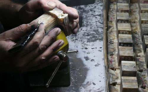 A craftsman known as a batim macher works on the protruding Shin on a head tefillin (Photo: Flash90/Nati Shohat)