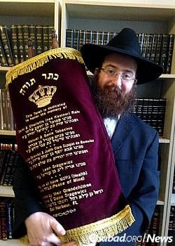 Rabbi Pinny Weinman, co-director of Chabad of Edinburgh, holds the Torah for use by Jewish students at the university (Photo: Bais Yisroel Torah Gemach)