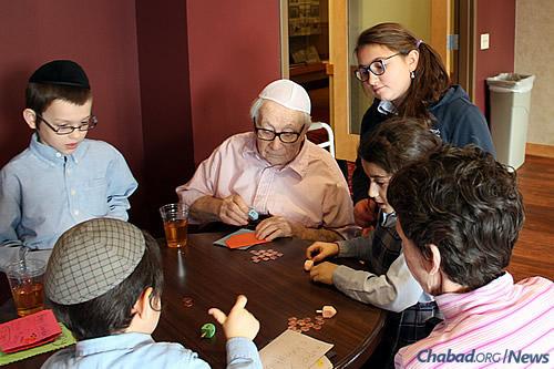 Playing dreidel at a local senior center, part of regular intergenerational programming.