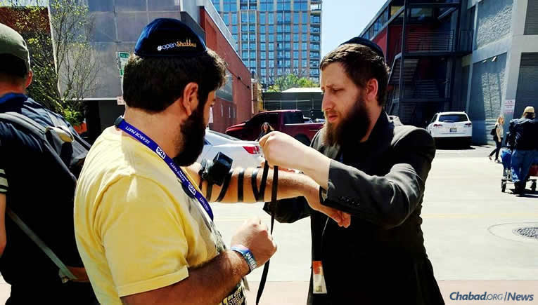 Rabbi Mordechai Lightstone, founder of Tech Tribe with his wife, Chana, wraps tefillin last year with a Jewish man at SXSW in Austin, Texas. They have been hosting an electronics-free Shabbat dinner at the festival since 2010; this year, a Purim party is also on tap, co-sponsored with local Chabad emissaries, the Levertovs, and Israel Bonds.