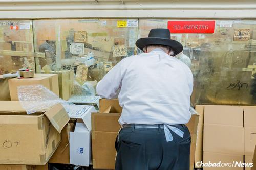 Packing up boxes of handmade shmurah matzah. (Photo: Eliyahu Parypa/Chabad.org)