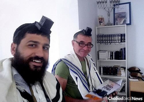 Rabbi Uri Medina of the newly opened Chabad of Rhodes, left, wraps tefillin with a fellow Jew on the Greek island. He will be part of a contingent of 23 rabbis expected at the European and Central African Regional Conference of Chabad-Lubavitch Emissaries, which starts on Sunday.