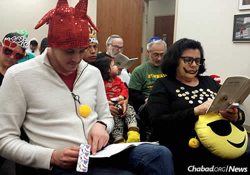 John Doherty, second row, an active community member who has called Indiana home for 15 years, hears the Megillah read on Purim. In front are Elyahu and Leah Herszberg.