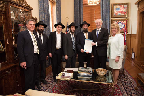 "Arkansas Gov. Asa Hutchinson displays the ""Education and Sharing Day"" proclamation at a ceremony attended by Chabad-Lubavitch emissaries based in the capital of Little Rock. From left are: State Rep. Charlie Collins, Rabbi Ben Tzion Pape, Mendel Ciment, Rabbi Yosef Kramer, Rabbi Pinchus Ciment, Hutchinson and State Rep. Robin Lundstrum (Photo: Randall Lee/Office of the Governor)"