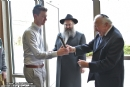 Artist Martin Lowenberg affixes historic Mezuzah Cover to front door of the Chabad Center