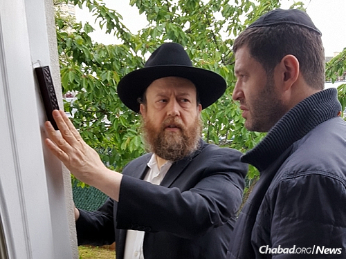 Brikman hangs a mezuzah for an area resident as part of a 2016 campaign to affix hundreds of them on neighborhood doorposts.