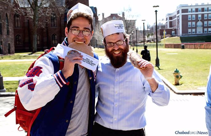 """Chabad at Wesleyan University in Middletown, Conn., co-directed by Rabbi Levi and Chani Schectman, has purchased a building to offer more space for services, Shabbat dinners, classes, student programs and Jewish holiday events. Here, the rabbi and Sam Wachsberger display homemade shmurah matzah made at a """"Model Matzah Bakery"""" workshop."""