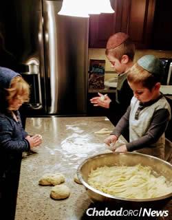 The Telsner children help prepare challah.