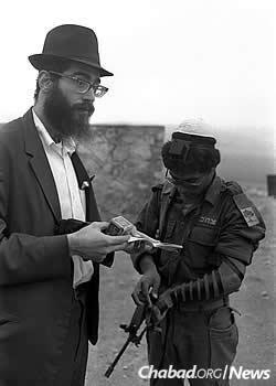 The late Rabbi Aharon Eliezer Ceitlin, left, wraps tefillin with an Israeli soldier at his post on the country's northern border in the winter of 1976. (Photo: Yaacov Sa'ar/Israel Government Press Office)