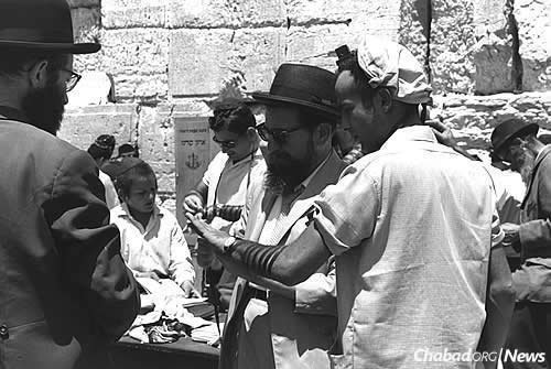 A Lubavitcher Chassid puts tefillin on with a visitor to the newly-opened Western Wall plaza on July 2, 1967. The Rebbe had sent a telegram to Chabad activists in Israel a few days earlier, instructing them to open a permanent tefillin booth at the Kotel and receive all the proper permits. (Photo: Fritz Cohen/Israel Government Press Office)