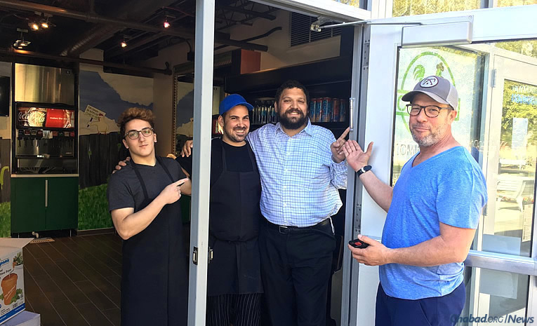 Pointing to the mezuzah affixed to the new Chick-In glatt-kosher restaurant at Arizona State University are, from left: Benjamin Muhlmann; Chef Mayaan Glass; Rabbi Shmuel Tiechtel, co-director of Chabad at ASU; and the owner of Chick-In, Yariv Elazar.