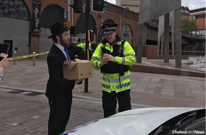 Rabbi Shneur Cohen of Chabad Manchester City Centre delivers danishes and hot tea to police officers outside the concert hall where a terrorist bomber killed at least 22 people, some of them children. (Photo: Emily Dugan/Twitter)