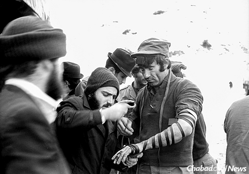 A Chabad Chassid puts on tefillin with an Israeli soldier on a military base in the 1970s. (Photo: JEM/The Living Archive)